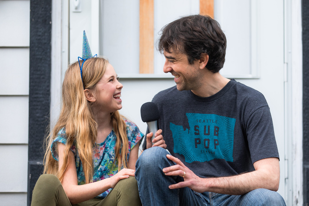 Jeremy Smith and his daughter, Rasa, on their front porch in the Rattlesnake Neighborhood of Missoula. The two host the podcast 'You Must Know Everything' together, and spend the short episodes discovering the answers and solutions to everyday questions, and sometime making unexpected connections.