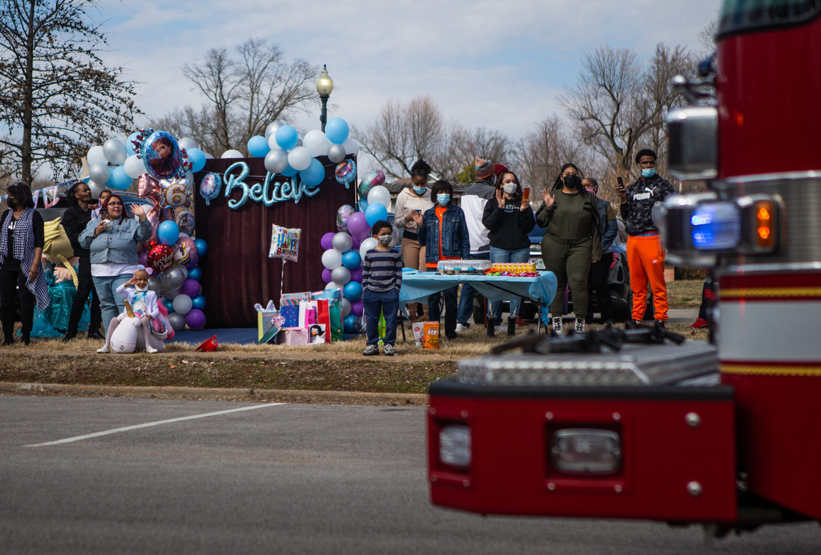 Paydenn Shelton, her family and friends watch fire trucks from around St. Louis proceed past January-Wabash Park in Ferguson during her birthday parade on March 6, 2021.