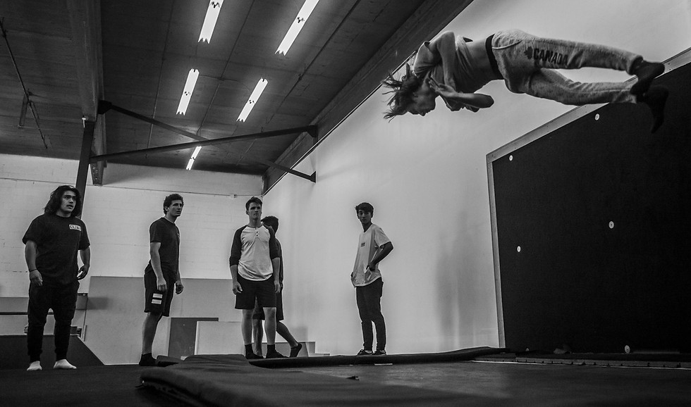 """Several athletes observe Linkin Orth practicing tricks on the trampoline in Unparalleled Movement on Oct. 19, 2018. Orth, from Couer D'Alene, was in town for Balls Jam, an 3-day event held in the parkour gym and around Missoula.  The event brought athletes from around the world to Missoula to train and socialize for the weekend. The gym hosts """"jams"""" to allow athletes to learn from each other in person.  """"You're physically seeing someone doing those things, and they're real,"""" said founder and co-owner Micah Marino, """"and it's really powerful when that starts to happen in younger generations."""""""