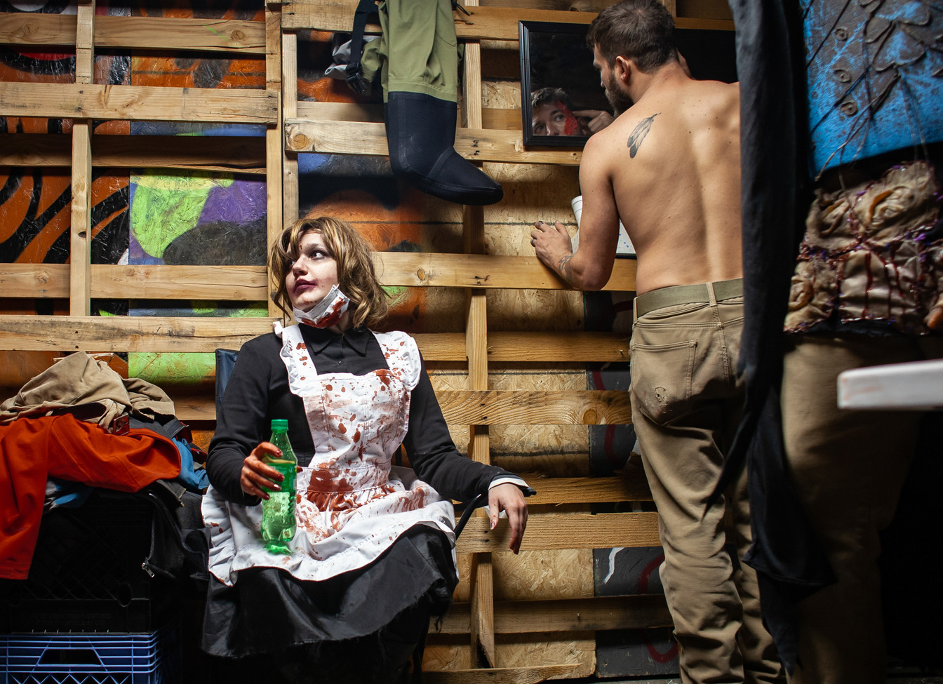 Missoula Haunted House scare-actress Max Randall, left, takes a break from makeup application while actor Bradley Lykins hurries to make changes to his makeup in the haunt's 'green room.' Lykins and his fellow haunters build Missoula's only haunted house from scratch each year, starting with an empty warehouse. A core group of about 20 designers and actors created this year's hellscape, which included a real river Styx, a functional boat, an airplane  crash and chainsaws.