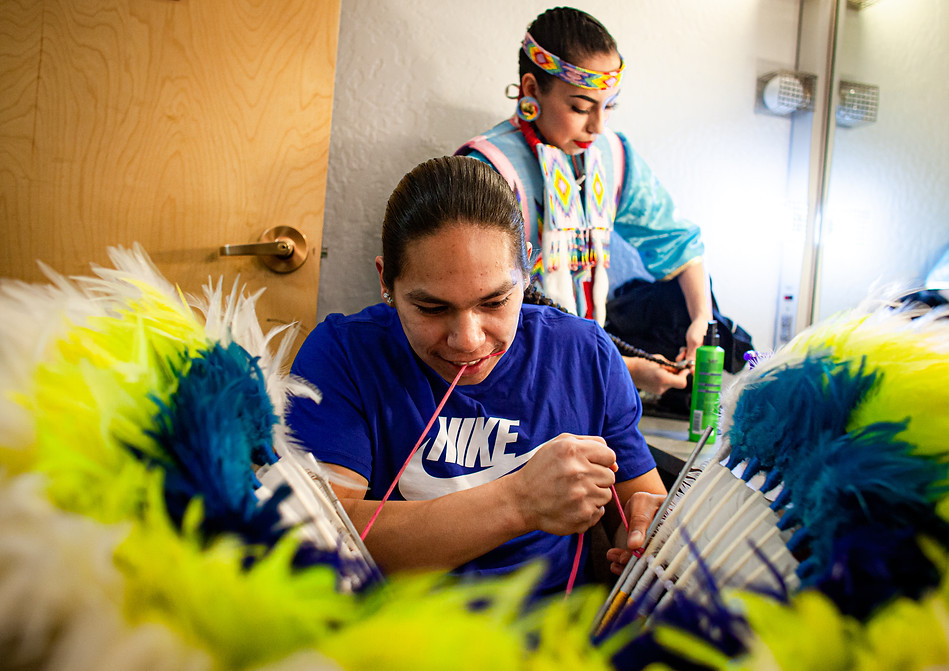 Chaz Baker makes last-minute adjustments to his regalia ahead of a small performance to open an event in Missoula on April 14, 2019. His sister, Aislyn Baker, helps him with his long braids. For the Bakers, dancing is a family affair. All three of Chaz Baker's siblings are competitive in several events at powwows and have been dancing since they were very young.