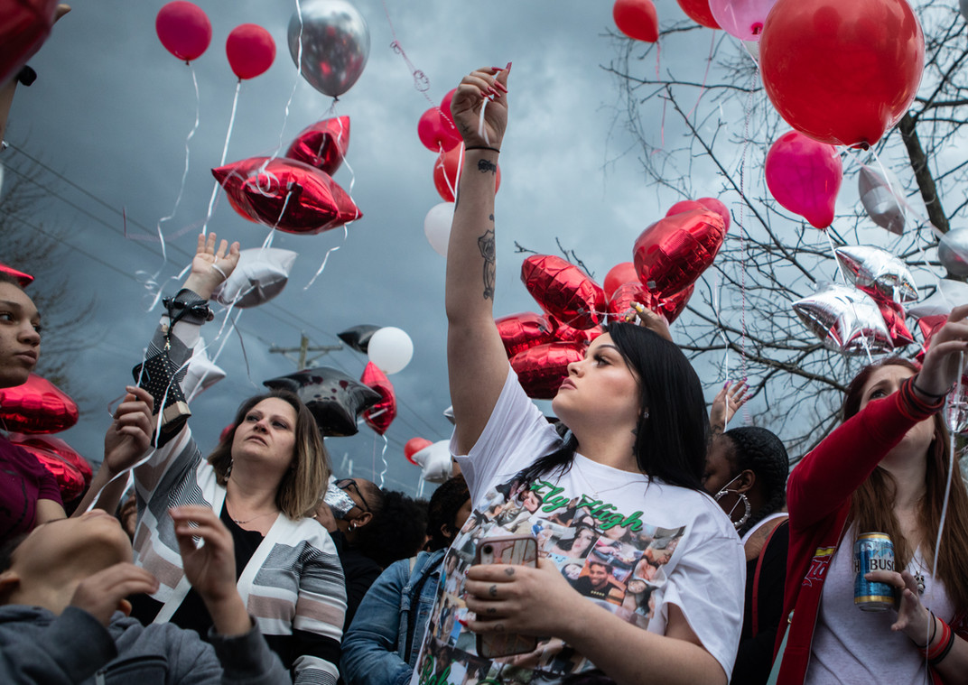 "Melissa Renfrow, second from right, girlfriend of shooting victim Craig Williams, releases a red balloon in his honor at a vigil held on March 30, 2021 in St. Louis after a neighbor fatally shot Williams a few days earlier during an armed standoff during which the neighbor believed Renfrow was at risk of being harmed. Renfrow is pregnant with Williams' child. ""He was my best friend,"" she said. ""I don't know what to do without him here."" Renfrow says Williams would never have hurt her, and is upset the shooter is not in police custody."