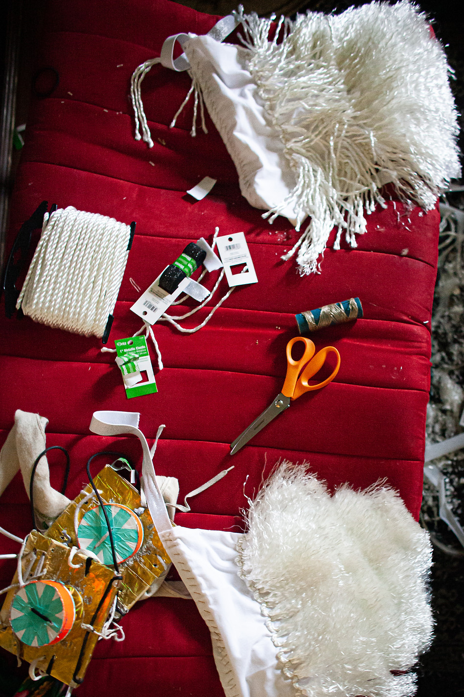 "Regalia repair materials sit scattered across many surfaces in Chaz Baker's apartment. Baker created his outfit with hours of stitching. The rest of his pieces include items from people he cares about so they're always with him while he dances. To make flashy ankle regalia for the upcoming competition, Baker used a white hand-towel from Walmart with the words ""Whip it Good"" printed on one side. On his shoulders, he uses camouflaged CDs for a unique shine - one is Dragon Ball-Z."