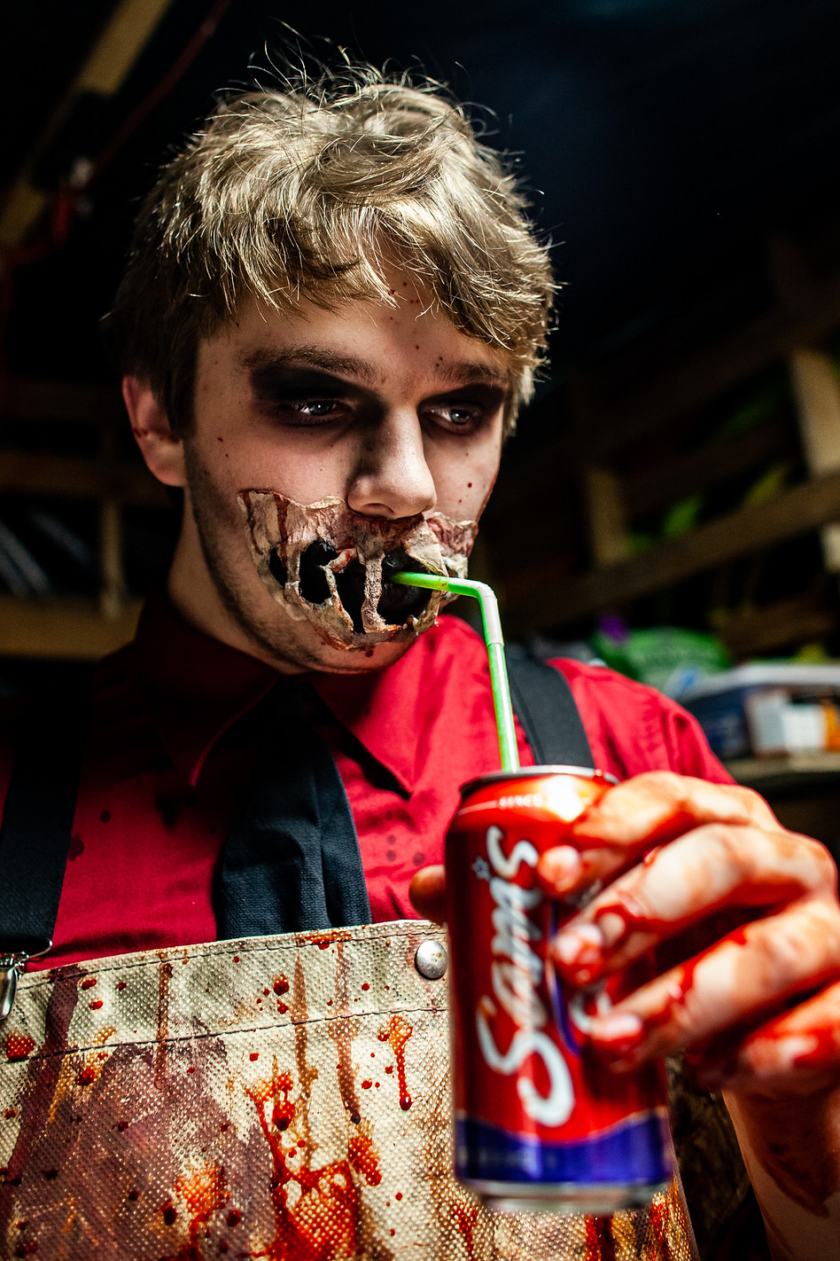 Scare-actor Logan Denison sips his soda through a straw fit between his prosthetic mouth makeup just before opening on Saturday night.  Denison is a first-time actor this year and plays a doctor in the war zone. He arrived an hour before opening to get sufficiently covered in blood and gore. The actors layer detail in their costumes, paying attention to things like prosthetics or shoes if they can, but prioritizing what the audience will pay the most attention to- the gore.