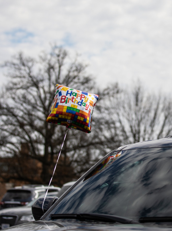 A balloon blows in the breeze, attached to a car preparing to participate in Paydenn Shelton's birthday parade in Ferguson on March 6, 2021