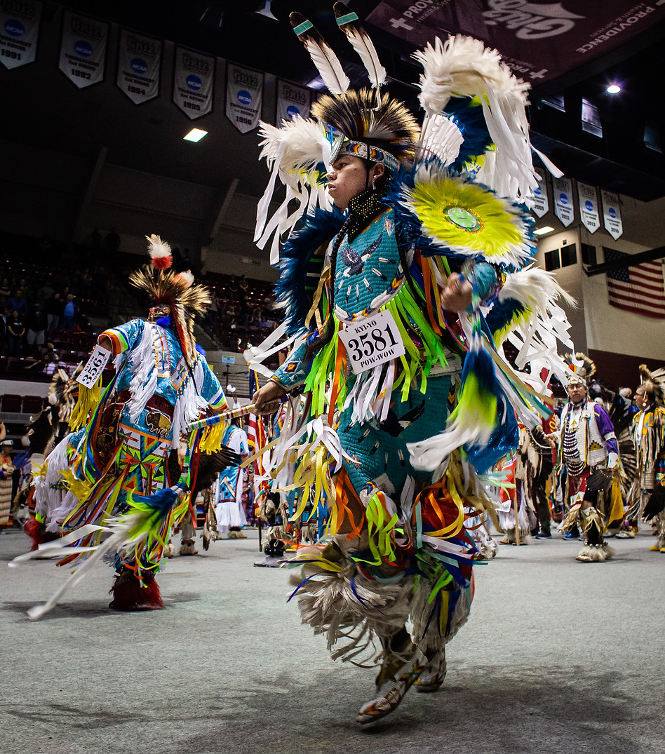 Chaz Baker dances in the Kyiyo Powwow Grand Entry at the University of Montana with hundreds of other dancers - ranging from young kids to experienced adults. Baker went on to win his age group for Fancy Dance, competing at 1 a.m. as the Powwow schedule fell behind. After winning, he treated his family to dinner.