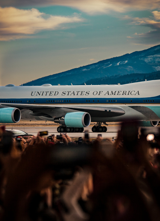 The crowd hold their phones overhead to get photos of Airforce One landing at the Missoula International Airport.