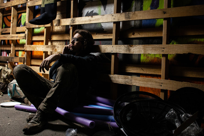 Davenport sits, exhausted, for a break to eat some pizza and chat on the phone as a busy evening in the warehouse wears on. Davenport balanced haunted house building with caring for a newborn baby at home during the last weeks before opening.
