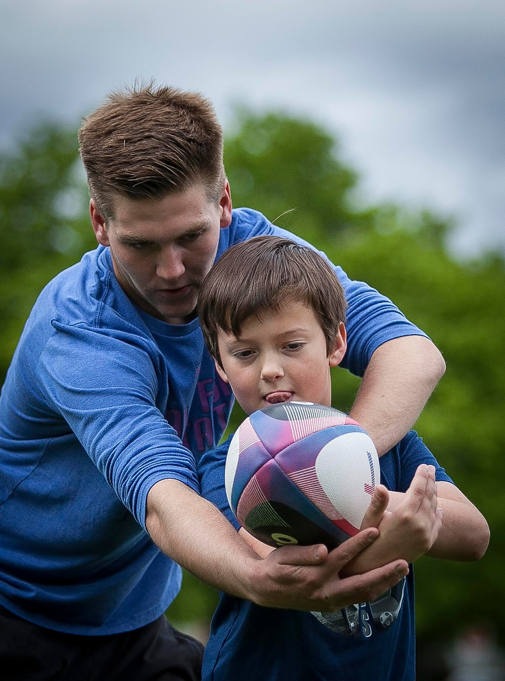 Rugby coach Colin Kelley shows Rugby Youth Camp attendee Jackson Fraser the proper technique for throwing a rugby ball at Missoula's Youth Day of Rugby on May 26, 2019. Fraser's parents say they brought him to the camp to see if he might be interested in playing rugby when he is older.