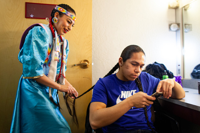 """Baker selects music for he and his siblings to dance to in a small performance opening for an event in Missoula while his younger sister, Aislyn, braids his long hair. """"I don't like cutting my hair,"""" Baker says. """"I like looking like an Indian. It anchors me to something."""""""