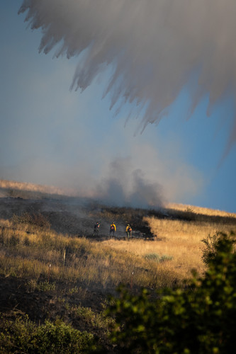 Three firefighters battle the Mount Sentinel above Missoula, Montana as a helicopter drops water from the Clark Fork River on the area. The blaze started near the University of Montana housing villages on Aug. 2, 2020 after two children playing with a lighter caught grass at the base of the moutain on fire.