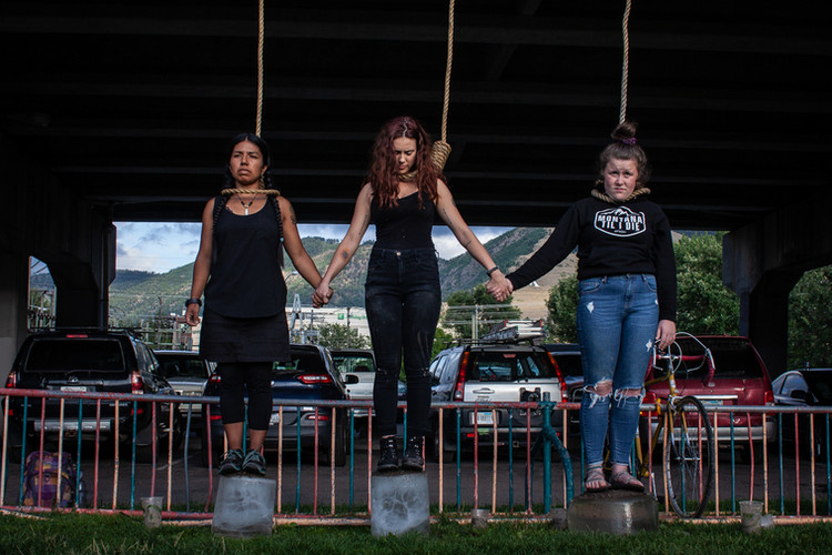 Climate protestors stand on ice blocks, holding hands under the Higgins Avenue Bridge in downtown Missoula with nooses hanging from above around their necks in order to emphasize the urgency of the climate situation. The demonstration took place on Aug. 22, 2019 in front of a crowded downtown park to raise awareness ahead of the world-wide school strikes for climate.