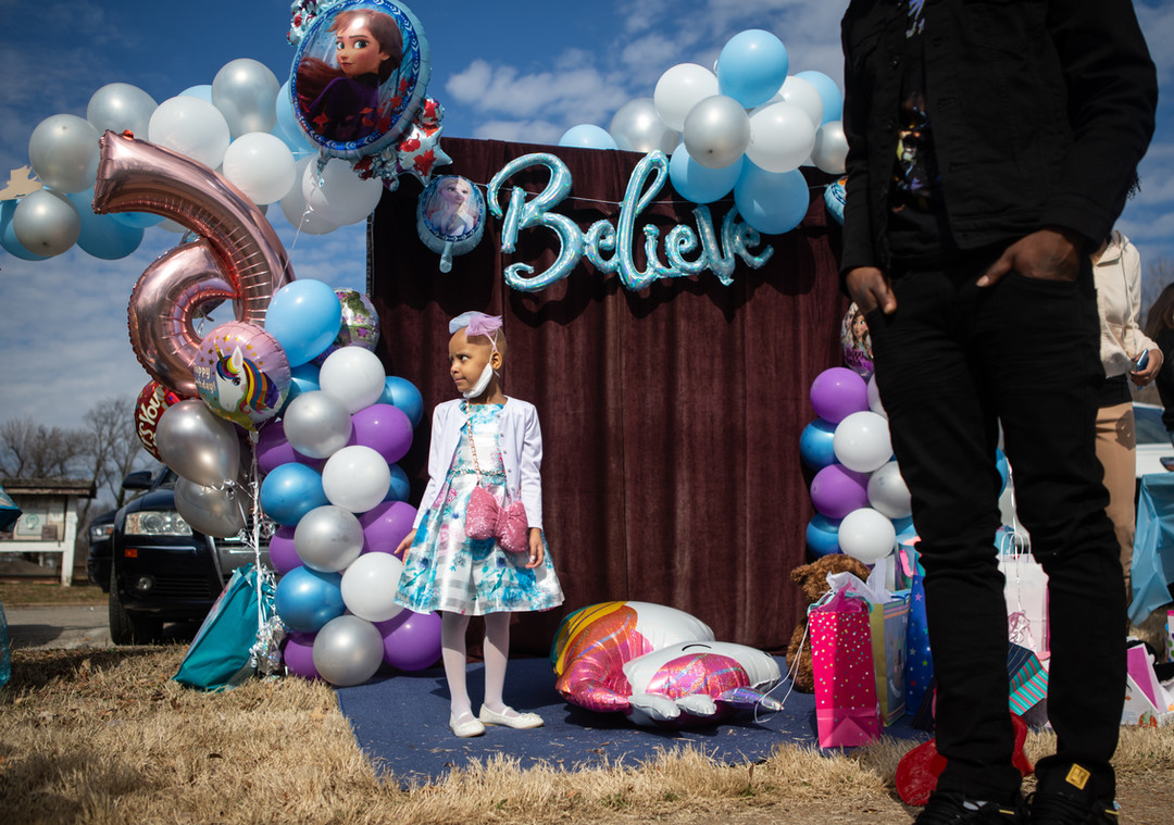 Paydenn Shelton stands among her birthday decorations with her father, Cody Mason, right, before her birthday parade at January-Wabash Park in Ferguson on March 6, 2021. Six-year-old Paydenn is battling a stage 4 neuroblastoma and could not have a typical birthday party due to COVID-19. Her mother and the Ferguson Police Department organized a drive-by parade for her, including the police, fire department and other community members.