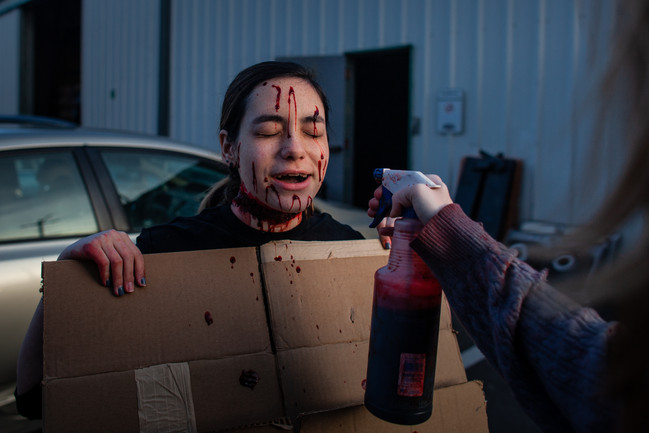 Scare-actress Gwen Campbell transforms into a sacrifice to Satan before opening on Saturday. To play the role, Campbell created a large neck wound out of latex and covered her face in fake blood.