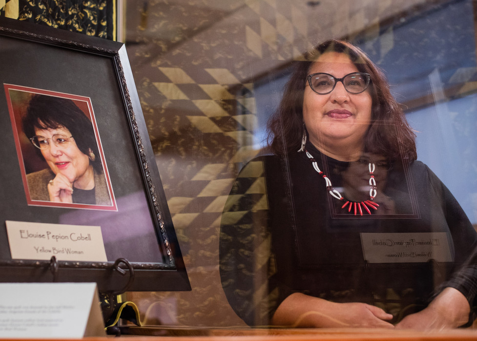 University of Montana S.E.A. Change Director Twila Old Coyote stands near a portrait of Elouise Cobell, a Blackfeet woman who Old Coyote says inspires her. Cobell sued the U.S. Government for mismanaging Native American trust funds. As the director of S.E.A.Change, Old Coyote will educate students in college, high school and middle school about gender equity.