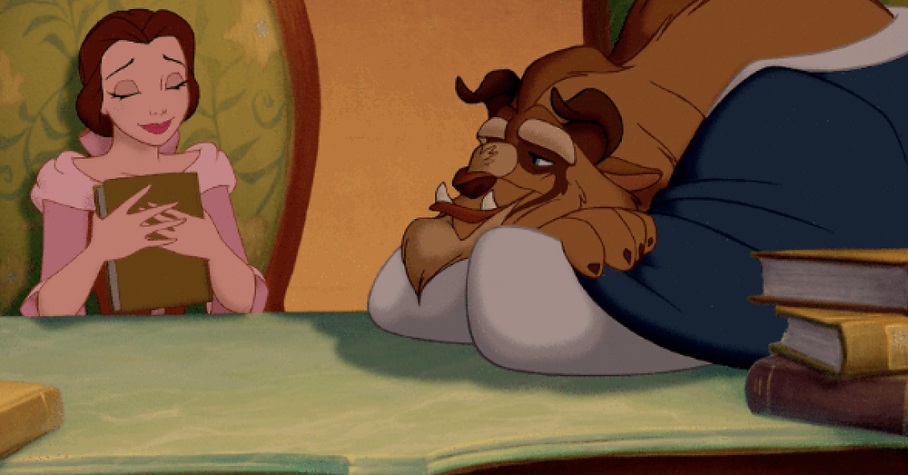 A screen cap from Beauty and the Beast where Belle is lovingly holding a book whilst the Beast gazes at her.