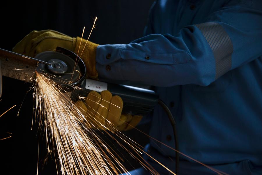 Trabajador de la industria portando overol ignífugo azul marca Texin FR con cortadora eléctrica sacando chispas.