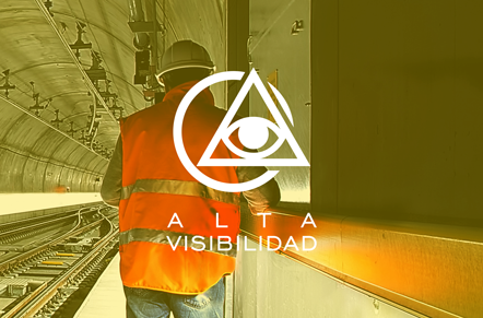 Trabajador de la industria con chaleco color naranja y casco con símbolo blanco de circulo con triángulo y un ojo con leyenda alta visibilidad.