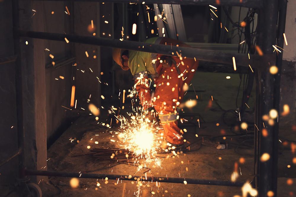 Trabajador con overol industrial naranja soldando y arrojando chispas rojas