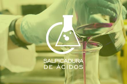 Manos con guantes de científico vertiendo liquido violeta de una matraz a otra con símbolo blanco de círculo y matraz con la leyenda salpicadura de ácidos.
