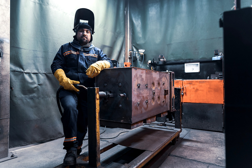 Trabajador, soldador portando overol ignífugo, careta y guantes dieléctricos amarillos.