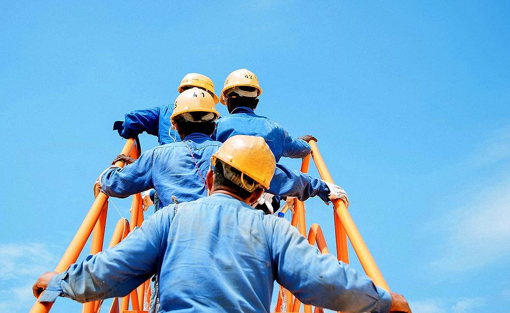 Trabajadores de la industria portando overol ignífugo azul marca Texin FR y casco naranja.