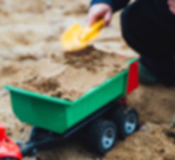 Child patting sand in a toy truck with spade
