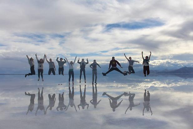 """Gruppe von zwölf Jugendlichen in einer Reihe, die in der Salzwiese """"Salar de Uyuni"""" in die Luft springen."""