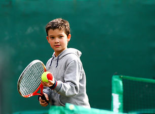 Little tennis player on a blurred green