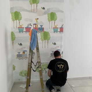 Playroom wallpaper being hung.