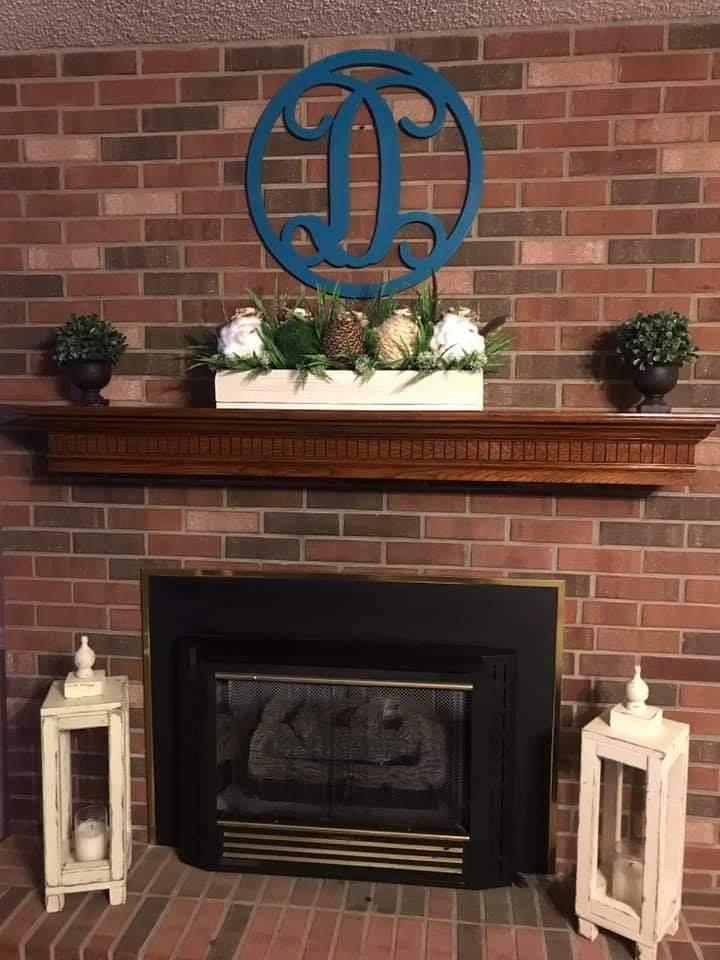 teal circle D on brick fireplace
