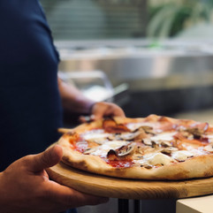 person-holding-whole-pan-of-baked-pizza-