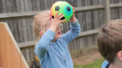 Activities for preschoolers - a toddler learning to head the ball during a football lesson - Tots in Sport