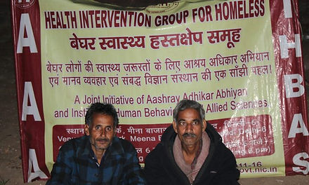 Two homeless men sitting infront of Health intervention group for homeless banner
