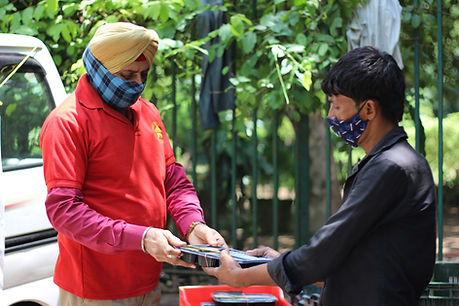 Aashray Adhikar Abhiyan worker giving food to homeless man