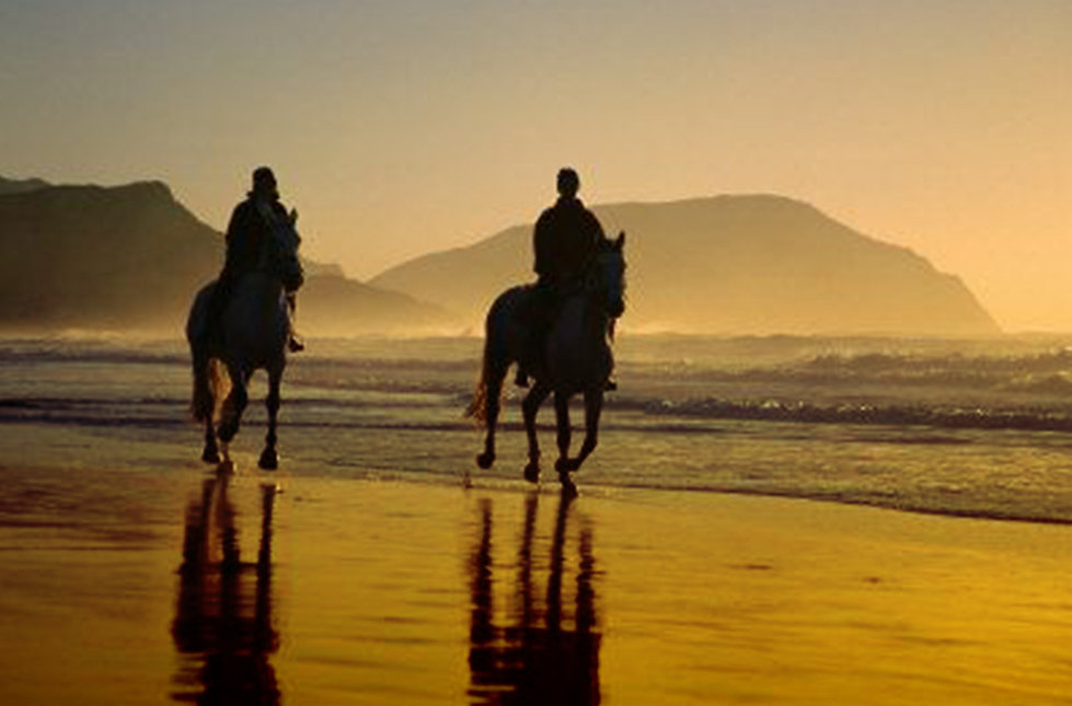 A couple are horseriding on a beach, Ker