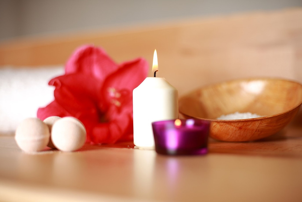 A flower, scented candle, and bath salts
