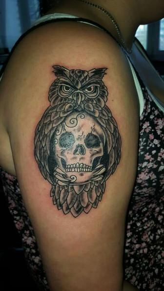 Totenkopf mit Eule Oberarm Tattoo