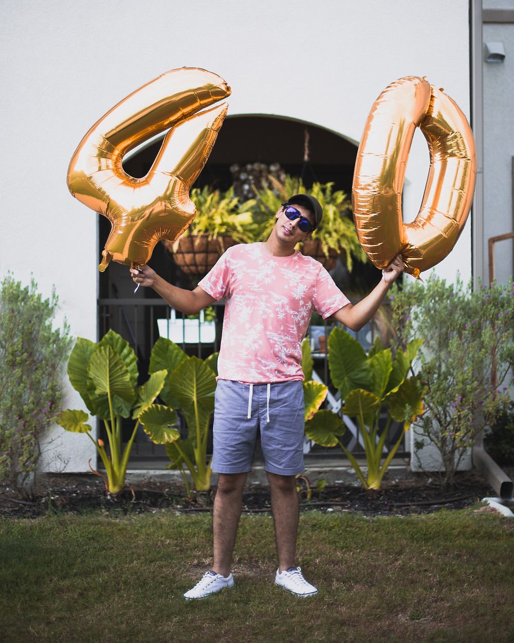 Carlos is holding two gold baloons, one is a  4 and the other is a 0