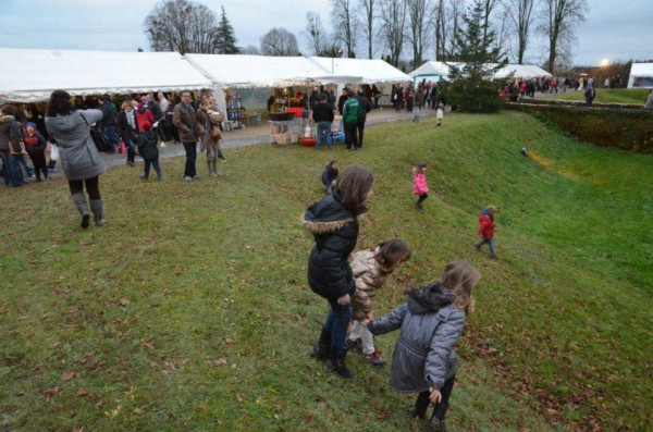 Children playing near the Château Bonneval Marché de Noël