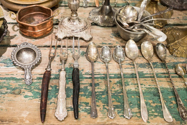 Vintage flatware and utensils grace a lush and rustic table