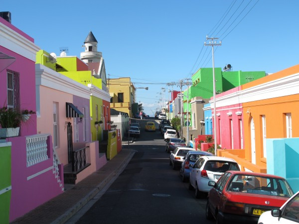 """Bo-Kaap"" or Upper Cape, in Afrikaans, is a somewhat mid-gentrification neighbourhood on a hillside overlooking the city of Cape Town. Originally known as The ""Malay Quarter"" for its rich cultural beginnings, the location has evolved into a bright, iconic South African tourist attraction. It is also the birthplace of Ukuva iAfrica."
