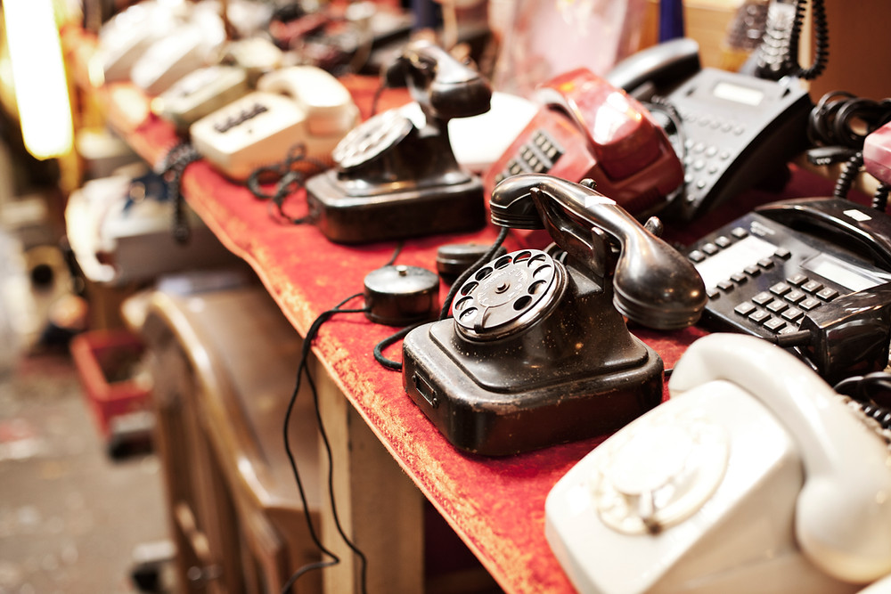 Many old analogue phones on a table