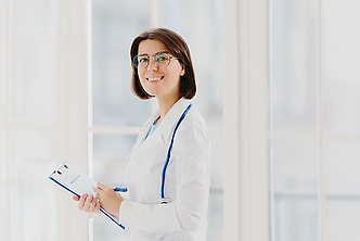 horizontal-shot-of-female-doctor-fills-up-medical-form-at-clipboard-stands-indoor-wears-ro