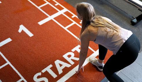 Junge Frau steht startbereit im Fitnessstudio um mit dem Training zu beginnen.