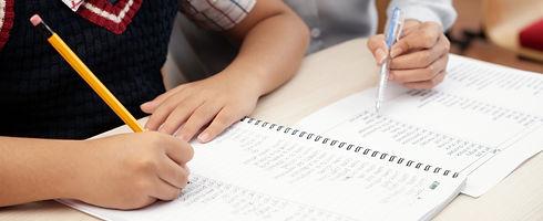 asian-schoolboy-writing-notebook-unrecog
