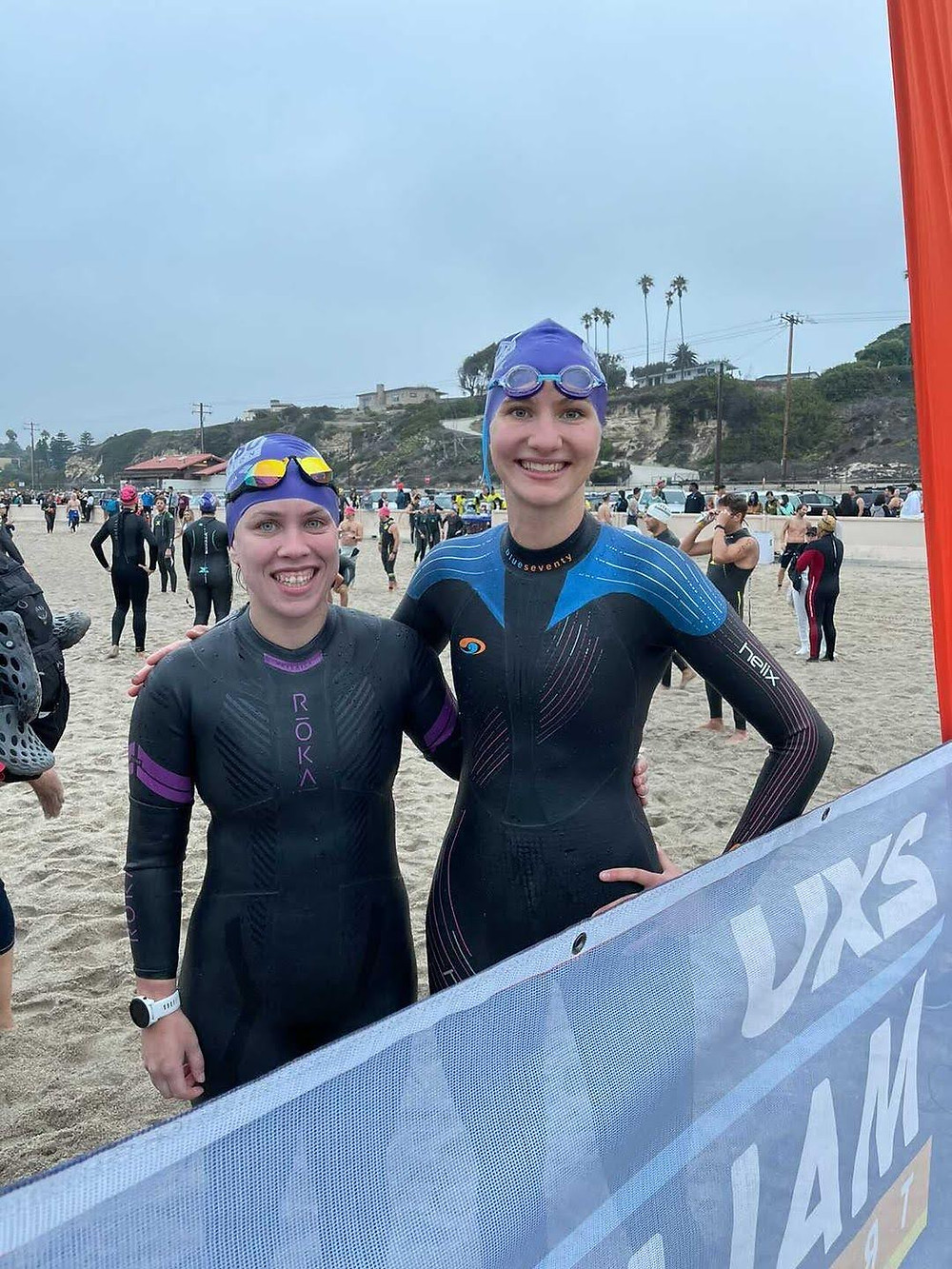 Two women in wetsuits on a beach