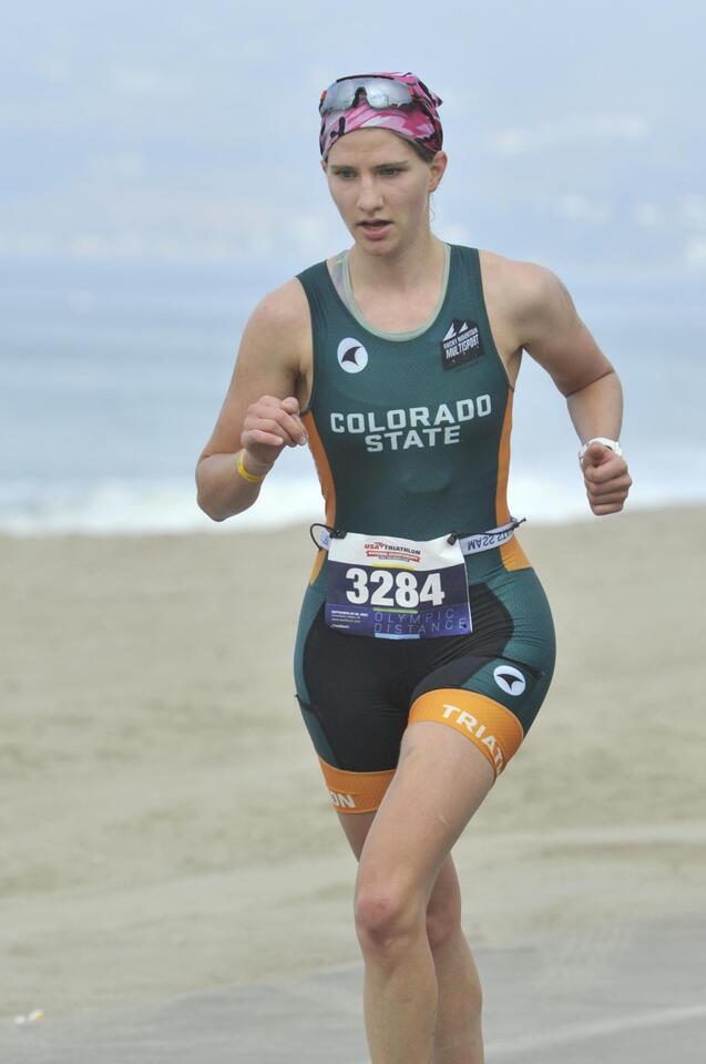 Girl running in a triathlon next to the ocean
