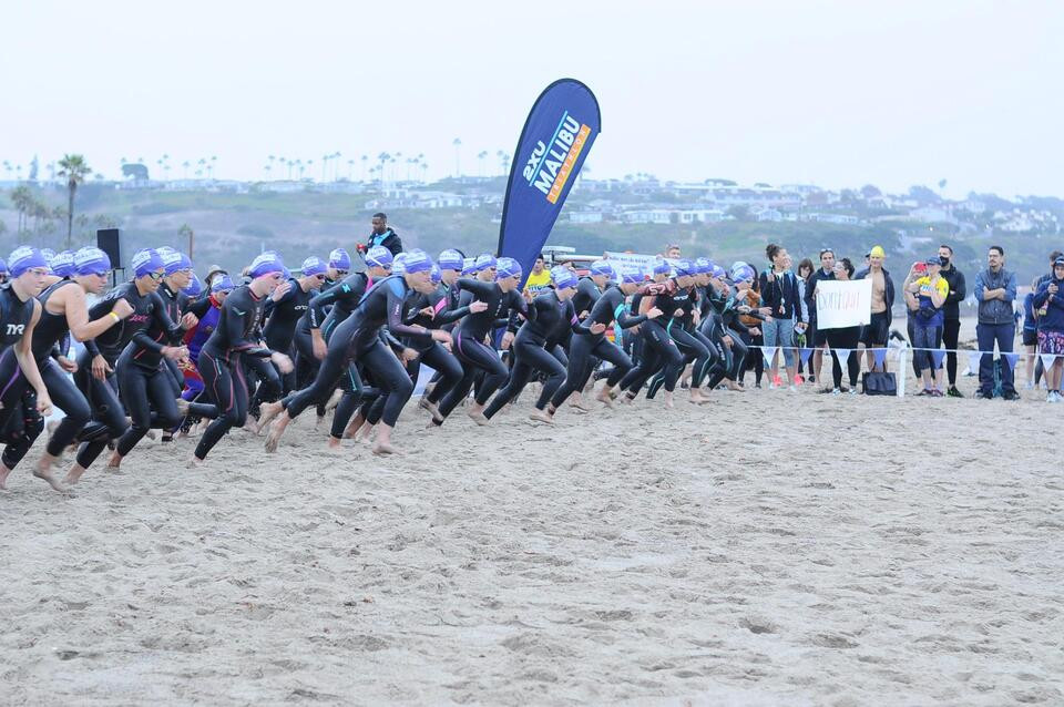 Women in wetsuits starting on the beach of a triathlon