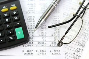 Picture of finance items, calculators, pen, glasses, spread sheet